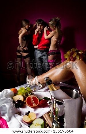 Guy having fun with woman decorated  by fruits and dancing stripteasers.  - stock photo