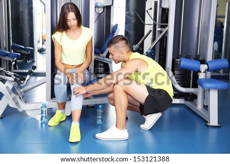 Guy help girl at gym