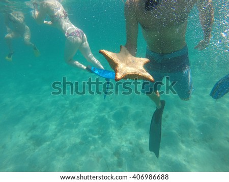 Guy holding a big yellow starfish (sea star) upside down underwater while snorkeling in Honduras - stock photo