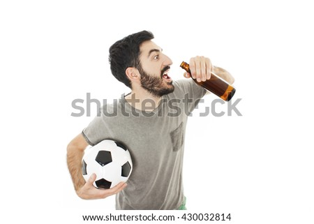Guy holding a soccer ball, drinks beer. Isolated on white background - stock photo