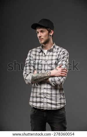 guy holds his hands together on his chest. dressed in a plaid shirt and a black cap. his body has tattoos and piercings in the ears - stock photo