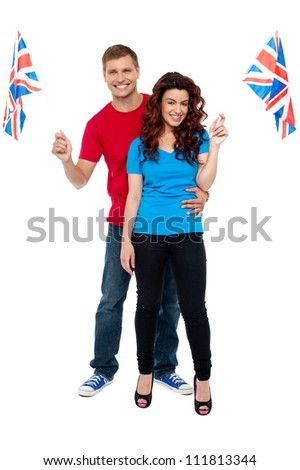 Guy hugging his girlfriend and both holding UK flag isolated over white background - stock photo