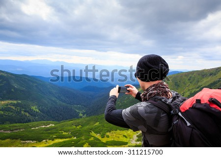 Guy in a campaign photographing mountain landscape background on mobile phone device. Series of photos. Dramatic cloudy sky. - stock photo