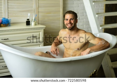Guy In Bathroom With Stairs On Background. Sexuality And Relaxation  Concept. Macho Sitting Naked