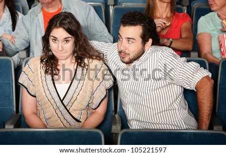 Guy in beard flirts with young woman in theater