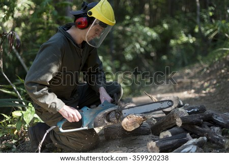 Guy in full green overall working with an electric chainsaw cutting into log. Shallow focus, sawdust flying around work area. Some cut up logs can be seen near work area.  - stock photo