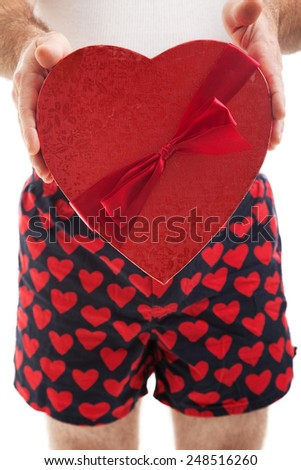 Guy in his heart boxer shorts giving a valentines day box of chocolates to you.,   - stock photo