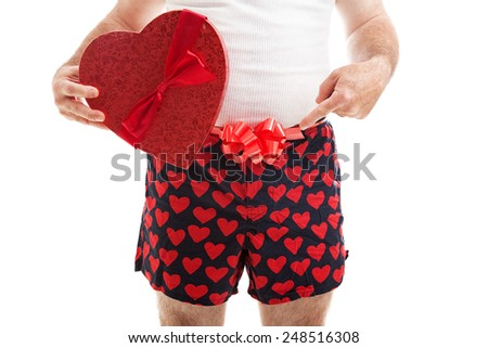Guy in his underwear with a Valentines Day gift and a bow around his underwear, pointing toward his crotch.  Isolated on white.   - stock photo