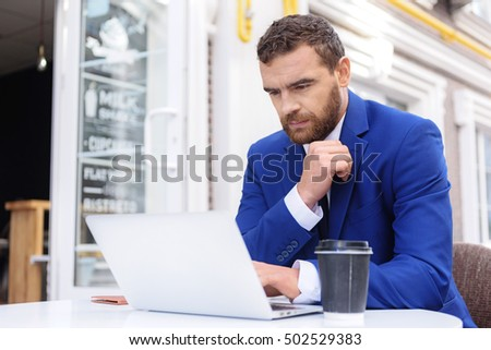 guy in suit sitting in front of laptop