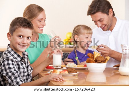 Guy is looking at the camera. His family has breakfast on background