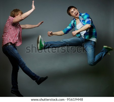 Guy jumping into air and kicking his friend, fool�s day series - stock photo
