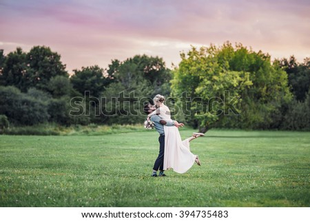 Guy lifted the girl. Couple on the meadow with tree.