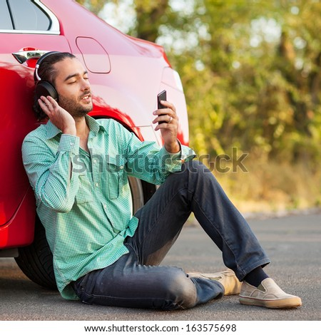 guy listening to music while sitting beside the car on the road - stock photo