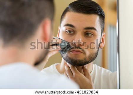 Guy looking at mirror and shaving mustache with electric razor - stock photo