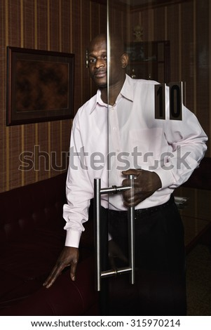 Guy looking out of dark office while opening the glass door - stock photo