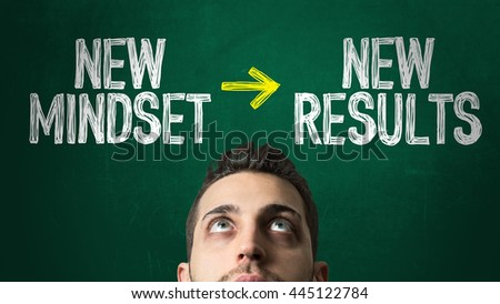 Guy Looking Up in a Chalkboard with the text: New Mindset -> New Results - stock photo