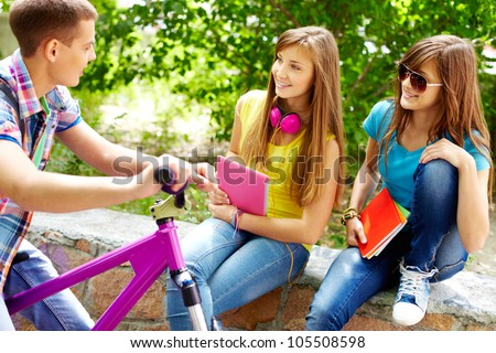 Guy on a bike hanging out with his school friends - stock photo