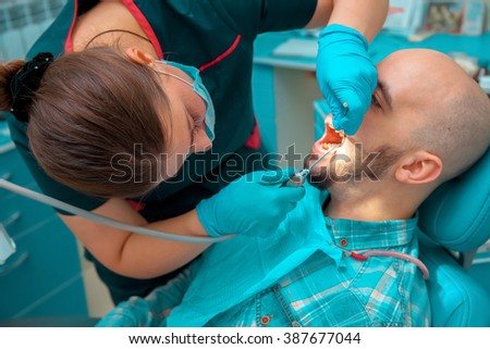 guy on the examination dentist checks the teeth. Medicine, dentist, health and stomatology concept