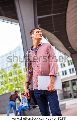 Guy on the modern street in casual clothing with laptop - stock photo