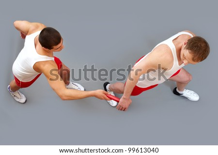 Guy passing the baton to his team member in the rush of a relay race - stock photo