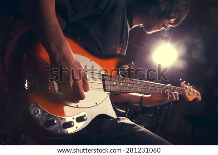 guy playing bass, guitar close-гз - stock photo