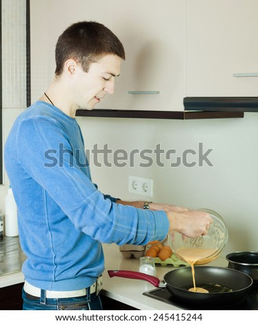 Guy pouring dough  in frying pan at the kitchen - stock photo