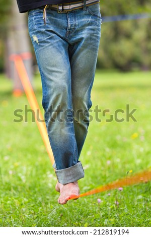 Guy practising slack line in the city park. Slacklining is a practice in balance that typically uses nylon or polyester webbing tensioned between two anchor points. - stock photo