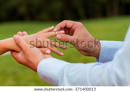 Guy puts the ring on the finger of his girlfriend. Guy makes a proposal to his girlfriend. Love confession. Hands of guy and girl close-up.