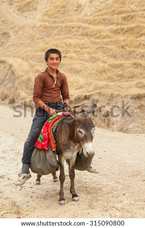 Guy riding on a donkey with a bag of pistachios