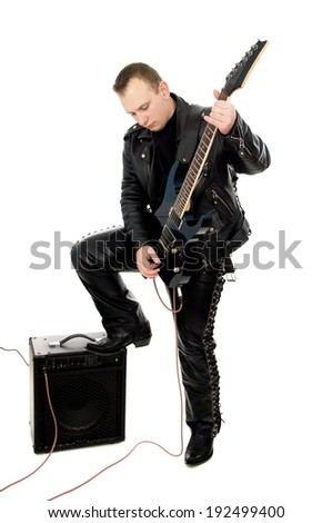 guy rock guitarist in leather garments, plays guitar isolated on white background - stock photo