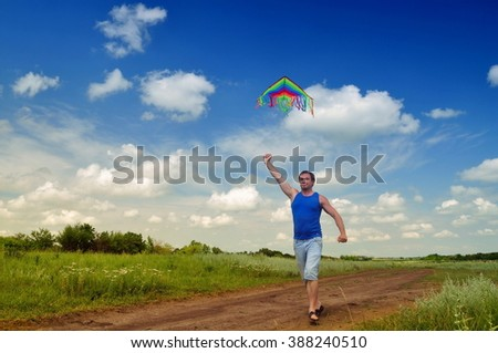 Guy running in a field with a kite - stock photo
