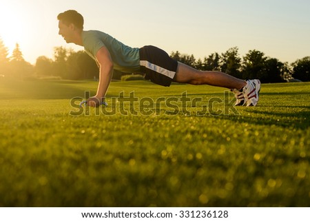 Guy shakes his muscles on the nature. Sports lifestyle. Young man engaged in sports in the street. Sports ground on nature. - stock photo