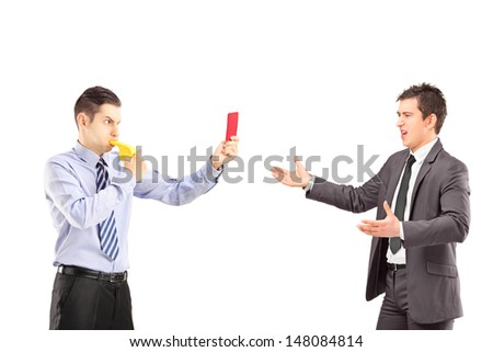Guy showing a red card and blowing a whistle to a young businessman in suit, isolated on white background - stock photo