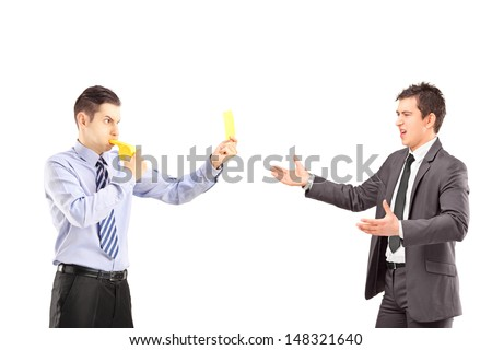Guy showing a yellow card and blowing a whistle to a young businessman in suit, isolated on white background - stock photo
