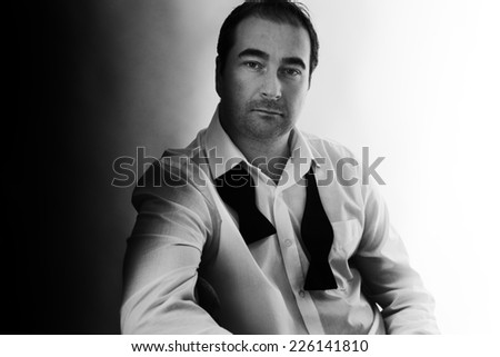 guy siting on a chair with a bow tie undone around his neck - stock photo