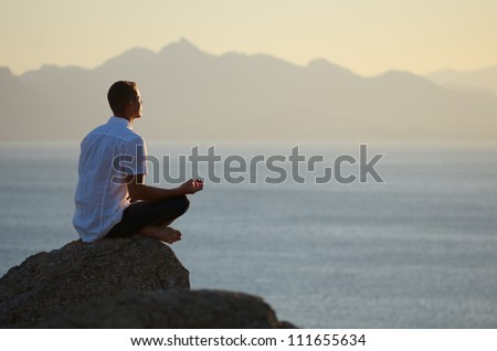 Guy sitting on a rock in the lotus position and looking at the setting sun - stock photo