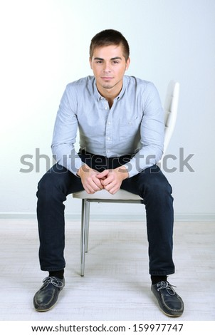 Guy sitting on chair in room