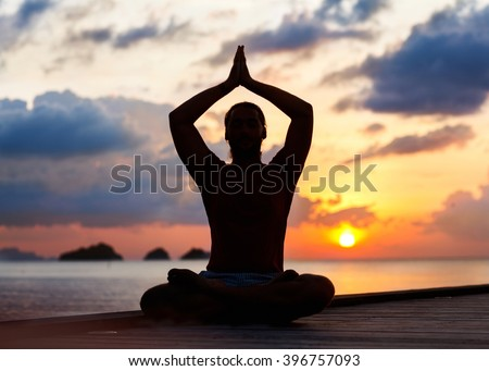 guy sitting on the sea and is engaged in yoga