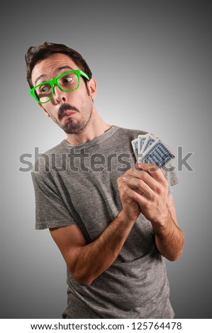 guy spying poker cards on grey background