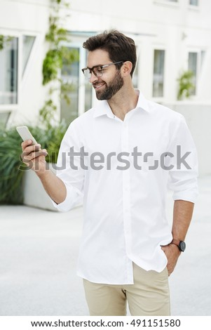 Guy texting on Smartphone and smiling