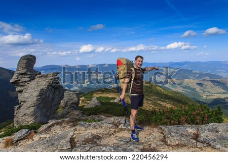 Guy traveler standing on a rock with backpack and indicates the direction. Autumn mountain travel.   - stock photo