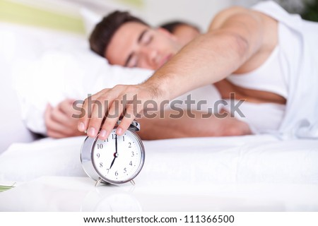 guy turning off alarm clock