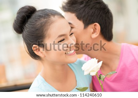 Guy whispering words of love in his girlfriend�¢??s ear - stock photo