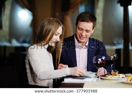 guy with a girl in a restaurant choose dishes from the menu