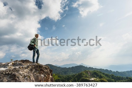 Guy with a travel backpack on the top of moumtain with beautiful valley background. Travel concept.