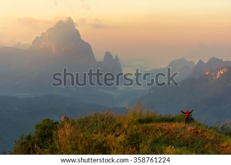 Guy with a travel on a top of a mountain - stock photo
