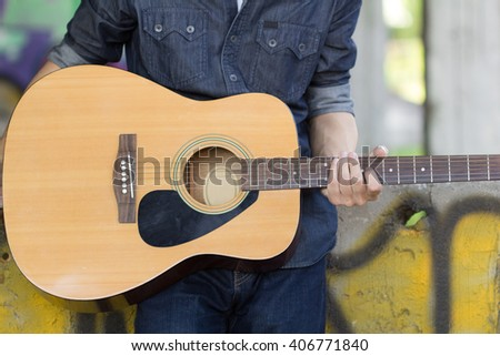 Guy with acoustic guitar outdoor - stock photo
