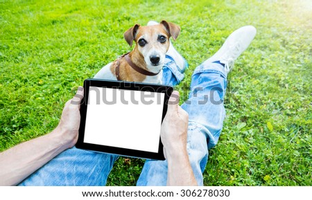 guy with dog sitting on green grass in the park and using a tablet pc/ Empty white space you can place your text. Happy summer time - stock photo