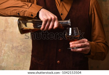 Guy with glass and bottle of cognac. Male hands pour brandy or whiskey into glass. Man holds alcoholic beverage on beige wall background. Service and tasting concept.