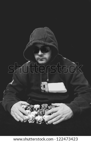 guy with glasses playing poker with chips in his hands